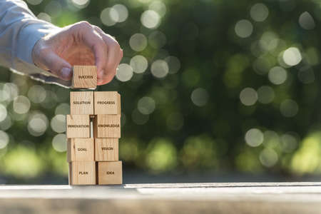 A conceptual image showing a mans hands placing wooden building blocks labeled with planning and success themed words in a brightly lit, outdoor park location. Фото со стока