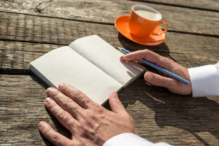 Closeup of the hands of a man ready to write in front of an open notebook with blank pages next to a coffee cup. Stock Photo