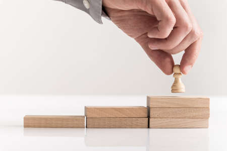 Businessman holding a pawn chess piece up steps to success formed by wooden blocks over white background.