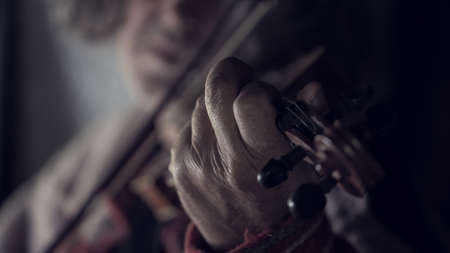 Retro toned image of the hand of an elderly man playing music on a violin indoors.