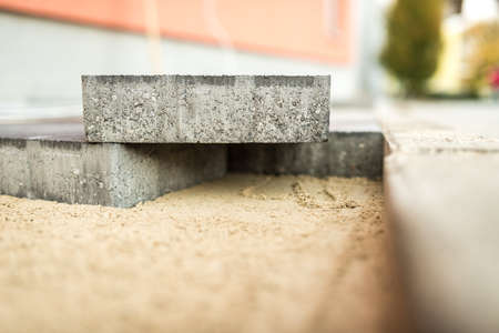 New paving bricks or stones on a prepared base in a construction and building concept. Stock Photo