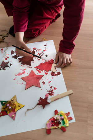 Young child painting Christmas decorations kneeling down on the floor with a box of festive red paint,top view.