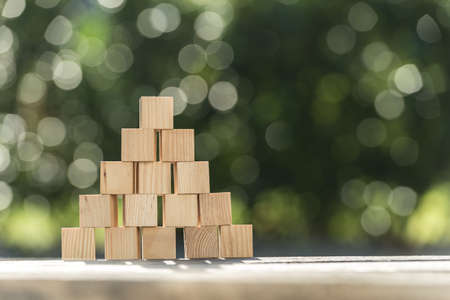 Pyramid of blank wooden blocks outdoors on a garden table with copy space. Stockfoto