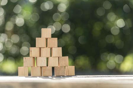 Pirámide de bloques de madera en blanco al aire libre en una mesa de jardín con espacio de copia.