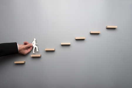 Homme d'affaires en chemise blanche, construire un graphique ou une échelle de succès sur fond gris. Banque d'images - 103916472