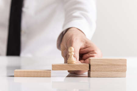 Businessman holding a pawn chess piece on a wooden block in a row of steps in a conceptual image.