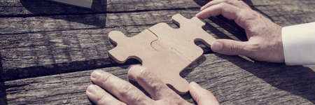Wide close up on unidentifiable business person with hands putting together two puzzle pieces on old wooden table, vintage effect toned image.