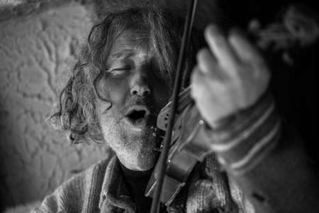 Greyscale black and white portrait of an elderly man singing as he plays a violin totally immersed in the music with his eyes closed in bliss.