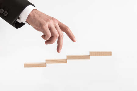 Businessman walking his fingers up steps formed by wooden blocks over white background.