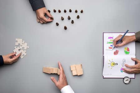 Vista superior del concepto de planificación empresarial y lluvia de ideas con un equipo de empresarios que organizan la estrategia mientras sostienen las piezas del rompecabezas, escriben ideas y juegan al ajedrez.