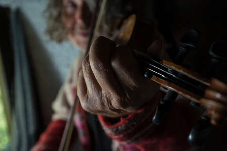 Man playing music on violin indoors with focus to his hand.
