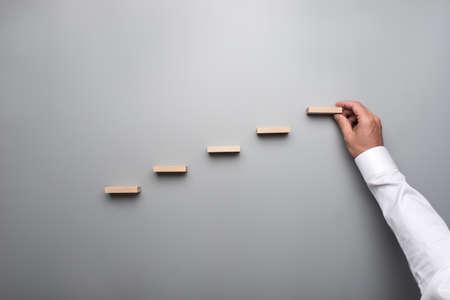 Hombre de negocios en camisa blanca construyendo un gráfico o escalera de éxito sobre fondo gris.