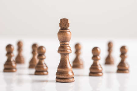 Black king with chess figures on white table in a conceptual image.