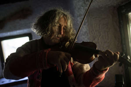 Elderly male musician with tousled long hair playing a classical violin at home in a head and shoulders portrait of him in a shadowy room with an absorbed expression.