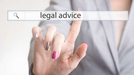 Female hand touching a website navigation bar with the text legal advice on a transparent virtual screen. Stock Photo