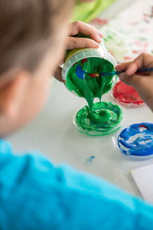 Little boy mixing colorful red, green and blue paints from jars for his art class in an over the shoulder view of him scooping the paint into the lid. Stock Photo