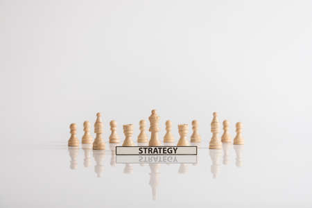 Wooden chess pieces strategy concept on a white background with copy space. Stock Photo