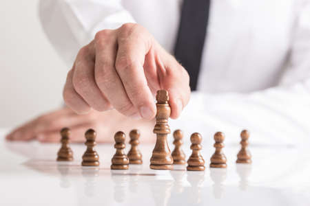 Businessman moving dark King chess piece at white table. Conceptual of business vision. Stok Fotoğraf