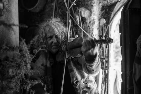 Greyscale image of an older bohemian man playing classical violin inside and old messy house.