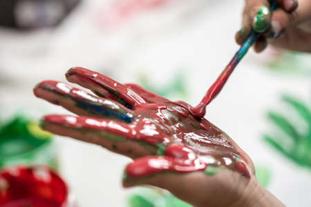 Child painting its hand with colorful red paint while creating artistic palm prints on a sheet of white paper in a close up view of him applying paint to his palm with a paintbrush. Banco de Imagens