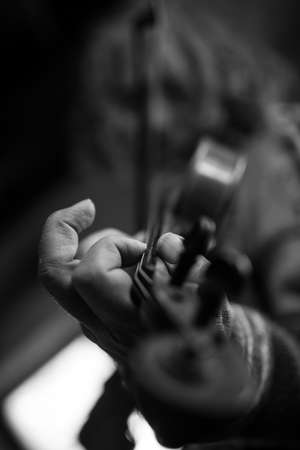 Greyscale image of elderly male musician with dirty nails playing a violin with shallow dof.