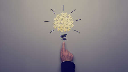 Retro toned image of a businessman pointing on a light bulb drawing with yellow puzzle pieces over grey background.