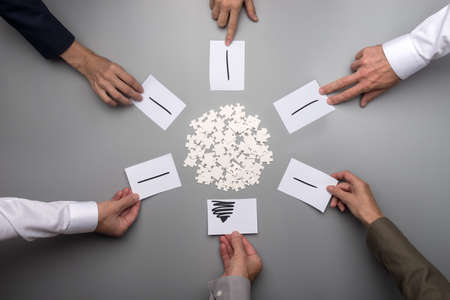 Six male and female hands in formal clothing placing papers with rays of light around white puzzle pieces scattered in a form of circle forming an image of light bulb.