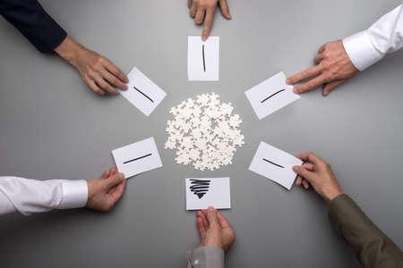 Sechs männliche und weibliche Hände in formeller Kleidung, die Papiere mit Lichtstrahlen um weiße Puzzleteile legen, die in Form eines Kreises verstreut sind und ein Bild der Glühbirne bilden.