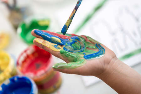 Child painting its hand with a paintbrush with colorful paint in a close up view of his palm. Banco de Imagens