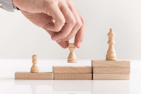 Businessman placing chess pieces on wooden blocks arranged as steps in a concept of corporate success in business, career and entrepreneurship in a close up view.