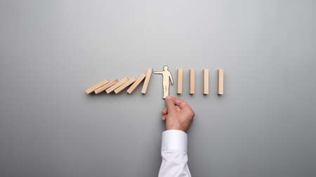 Top view of the hand of a businessman offering support to the silhouette of a paper man against the risk of a domino effect.
