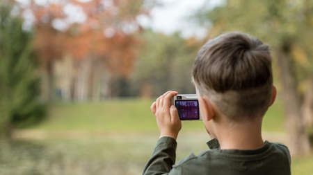 Boy photographing nature with a compact camera outdoors at park. Banco de Imagens