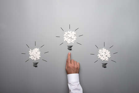 Three light bulbs formed by scattered white puzzle pieces with hand of a businessman pointing towards the bulb in the middle. Over grey background.