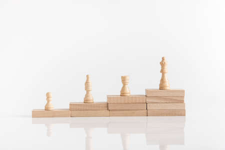 White chess pieces on a stepped stack of wooden blocks with queen piece on the highest level in conceptual image.