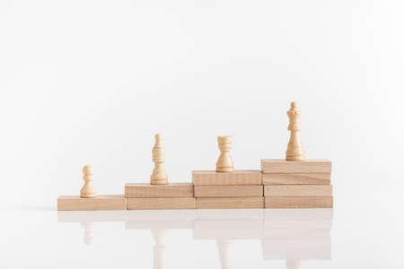 Pièces d'échecs blanches sur une pile de blocs en bois avec pièce de la reine au plus haut niveau de l'image conceptuelle. Banque d'images