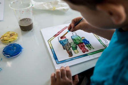 Young boy coloring in an outline sketch of a family in a house with paint carefully filling in the silhouettes with bright colours.