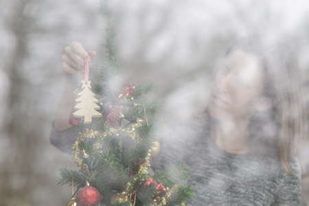 Woman hanging Christmas decorations on a tree viewed though a glass window with reflections of trees outside. Stock Photo - 106623705