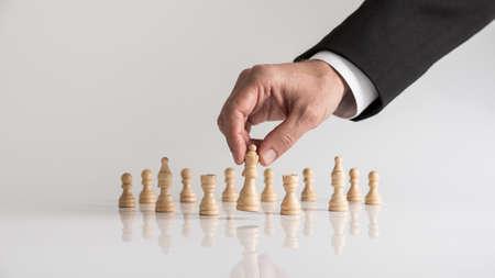 Hombre en traje de negocios jugando al ajedrez moviendo la pieza de la reina levantándola en sus dedos. Conceptual de planificación estratégica. Foto de archivo