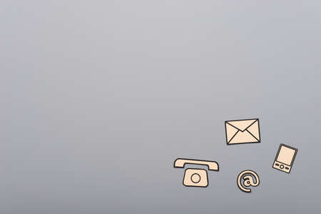 Contact and communication icons, phone, at sign, mobile and mail, on gray background with copy space.