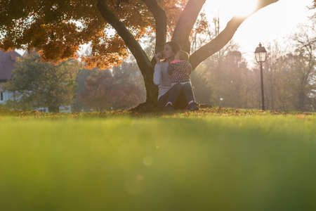 Young mother sitting under a tree with colorful autumn foliage with her baby girl on her lap in a low angle view across the grass with sun flare.
