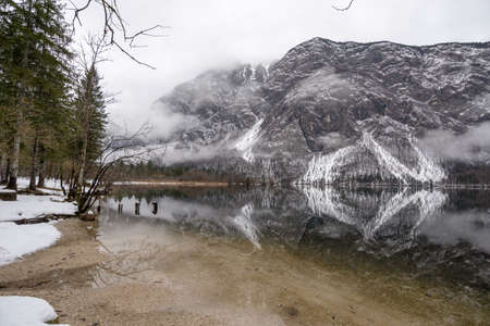 Tranquil winter lake in the mountains with snowy mountain peaks reflecting in the water and whisp of mist over the lake.
