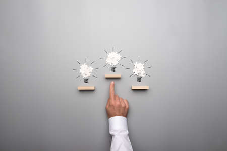 Three light bulb formed by white puzzle pieces placed on wooden pegs positioned as winner steps. Businessmans hand pointing towards the top bulb. Banco de Imagens
