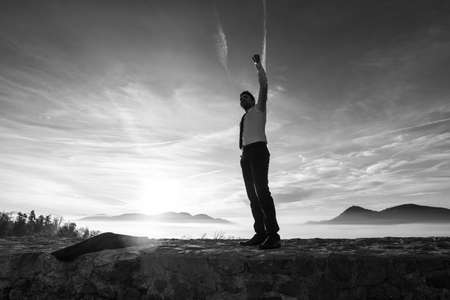 Businessman holding aloft his fist at sunrise celebrating his success and achievement as he stands on a wall with a misty mountain scene silhouetted against the bright sky, monochrome image. Banco de Imagens