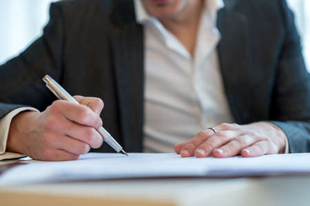 Closeup view of a businessman holding an ink pen to sign a contact or document.
