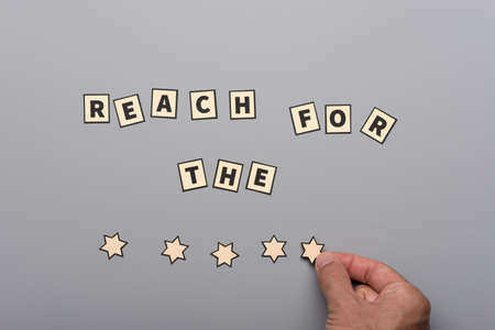 Reach for the stars saying assembled from paper cut letters and stars with male hand placing a star over grey background. Stock Photo