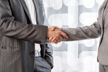 Closeup view of businessman and businesswoman shaking hands.
