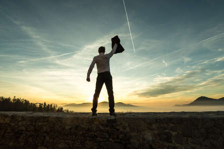 Businessman holding aloft his jacket at sunset as he stands on a wall overlooking a misty mountain scene silhouetted against the bright colorful sky with contrails. 免版税图像