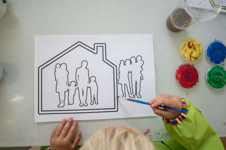 Top view of toddler boy or girl colouring a house with family silhouette printed on white paper.