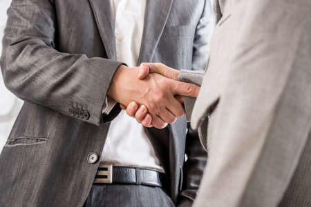 Closeup of business man and woman shaking hands in agreement.
