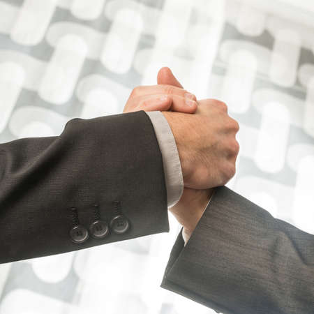Business man and woman shaking hands in greeting. Closeup square format view.